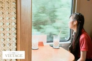 A young student looks dreamily out of a train window
